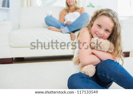 Daughter hugging her teddy bear while her mother is resting on the sofa - stock photo