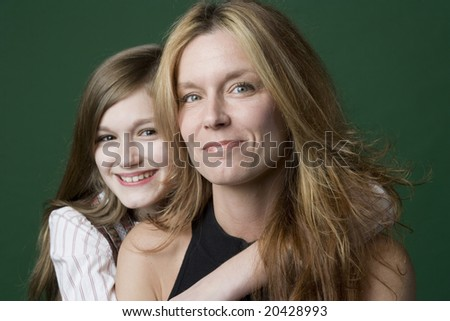 Daughter hugging Mom from behind - stock photo