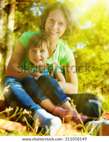 Daughter hugging mother on a bright sunny day. - stock photo
