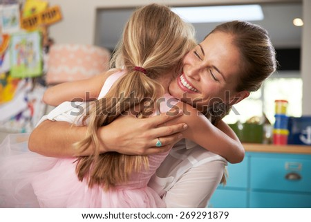 Daughter Hugging Mother Returning From Work - stock photo