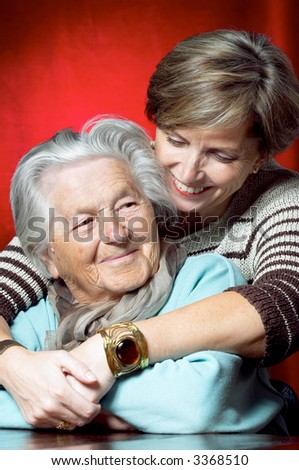 Daughter hugs her senior mother and smiles