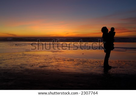 Daughter in her mother's arms and mom herself silhouetted by the sunset on beach in San Francisco.
