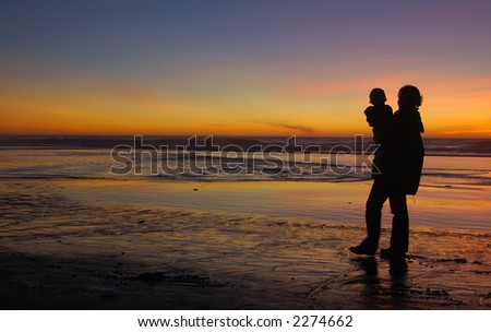 Daughter in her mother's arms silhouetted at sunset at Pacific. Mother's left leg is motion-blurred.