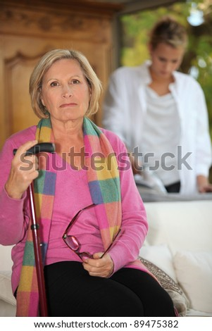 Daughter ironing for mother - stock photo