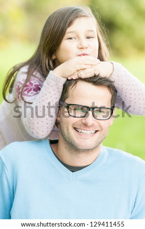 Daughter keeping her hands on father's head. Happy kid and dad having fun in park. Handsome man with glasses in blue jumper. Smiling parent and child enjoy outside. Family outdoor activity. - stock photo