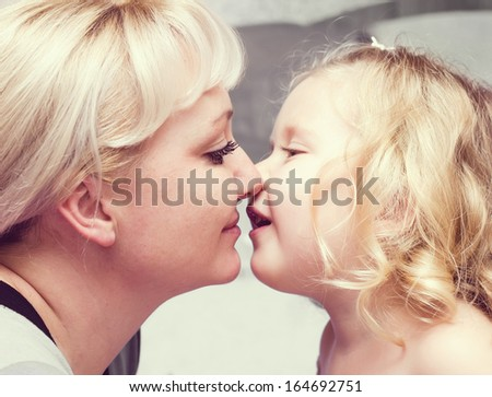 Daughter kissing her  Mother  - stock photo