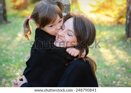 daughter kissing her mother in the park. - stock photo