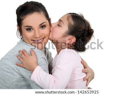 Daughter kissing her mum - stock photo