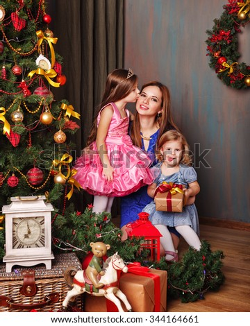 Daughter kissing mother near Christmas tree. Mother holds the youngest daughter in her arms. New Year. Holiday and fun. Merry Christmas. 2017 - stock photo