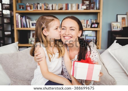 Daughter kissing mother with gift box while sitting on sofa at home - stock photo