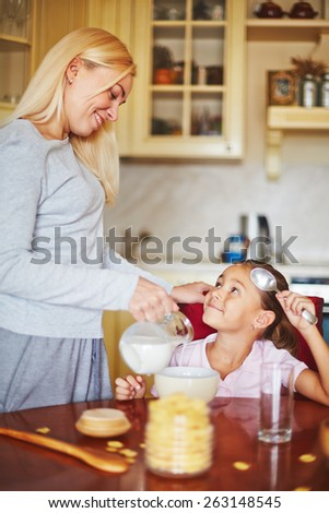 Daughter looking at mother and waiting for her milk and cornflakes - stock photo