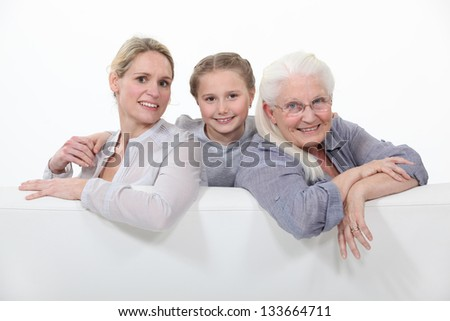 daughter, mother and grandmother sitting on the couch - stock photo