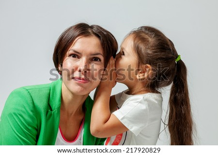 daughter mother whispers in the ear of his secret - stock photo
