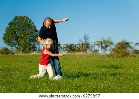 Daughter playing her dad out in a soccer game on a meadow