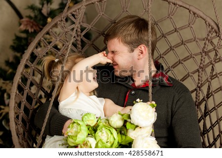 Daughter plays with dad. Babe caught father's nose and man's eyes were closed. Funny family photo. Blonde girl in a white dress sitting on dad's lap