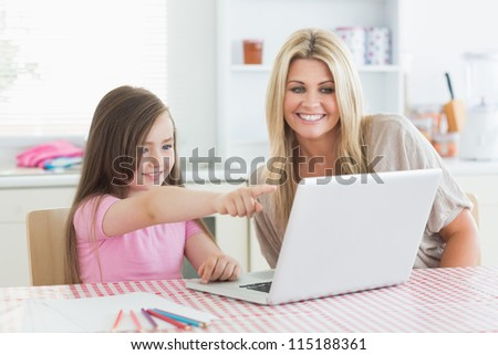 Daughter pointing at laptop with mother in the kitchen - stock photo