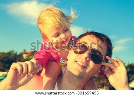 Daughter sat on father's shoulders. Man and child laughing and holding hands. Sunglasses reflected sunset and sea. Toned image