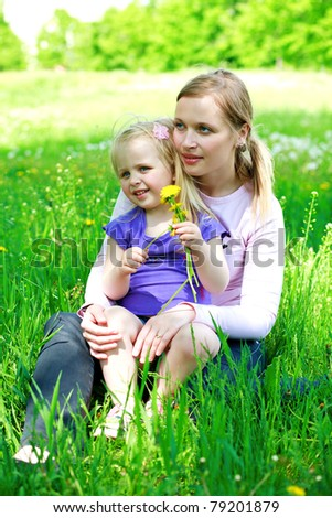 Daughter sits on mother on a grass outdoors with a dandelion