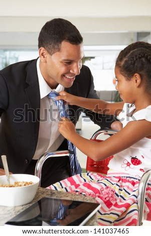 Daughter Straightens Father's Tie Before He Leaves For Work - stock photo