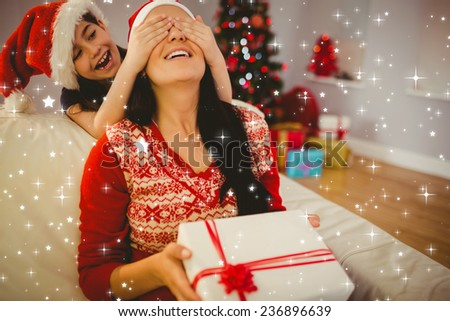 Daughter surprising her mother with christmas gift against twinkling stars - stock photo