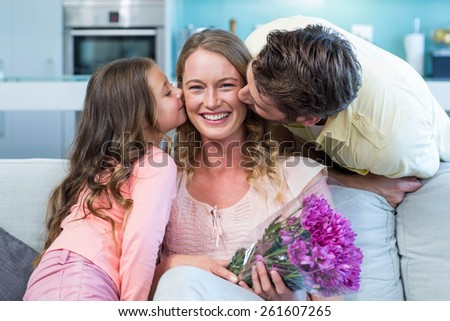 Daughter surprising mother with flowers at home in the living room - stock photo