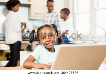 Daughter using laptop against parents in the kitchen