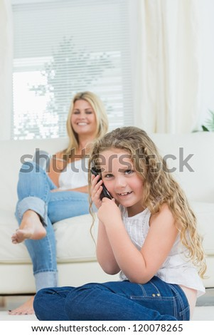 Daughter using mobile phone while her mother laughing on the sofa - stock photo