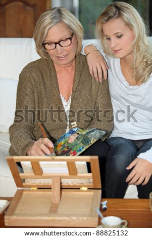 Daughter watching mother paint - stock photo