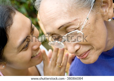 Daughter whisper some funny secret to her old mother - stock photo