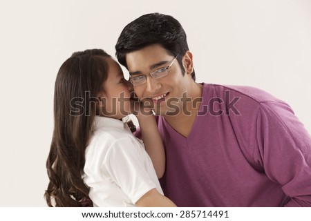 Daughter whispering in father's ear - stock photo