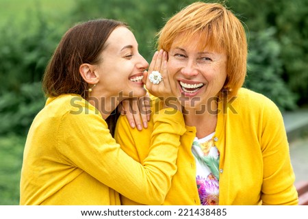 Daughter whispering something to her mother in the park - stock photo
