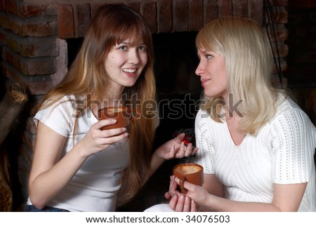 Daughter with mother communicate near a fireplace - stock photo