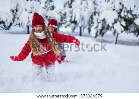 daughter with mother play in snow-covered park in winter