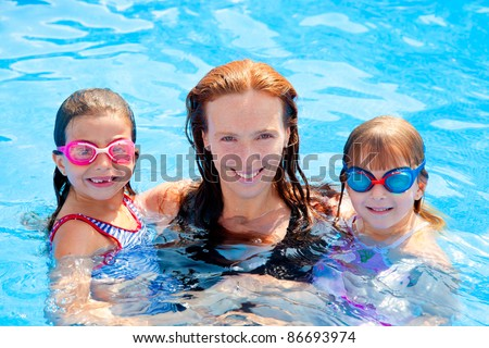 daughters and mother family swimming in pool on summer vacation - stock photo