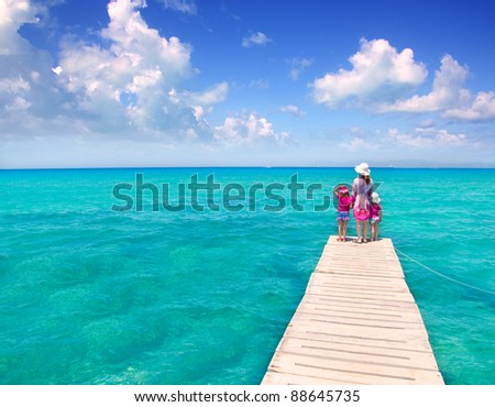 Daughters and mother in jetty on Formentera with turquoise sea - stock photo