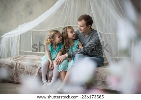 daughters being playful in bed and having fun while at home with father, interior. - stock photo