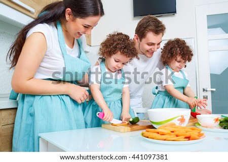 Daughters twins, dad and mom cook in the kitchen. A happy family. Parents teach their children to cook. Funny, curly twins with mom and dad in the kitchen. Education, education of children. - stock photo