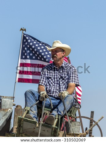 Davenport, WA. USA - Aug 22, 2015. A cowboy in the seat with a flag behind him at the Davenport, Washington vintage harvest August 22, 2015. - stock photo