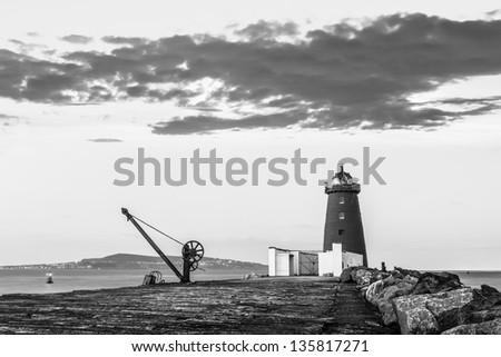 Davit and Lighthouse on a breakwater in Dublin bay in monochrome - stock photo