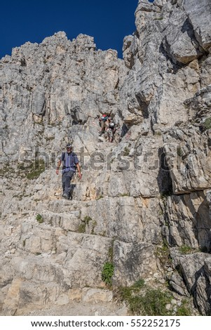 Davoi ridge, above Coronelle refuge, Catinaccio group-August 23, 2016: Hikers descending on trail 550 from Coronelle pass down to Coronelle refuge, Dolomites, Vigo de Fassa village,  Trento, Italy