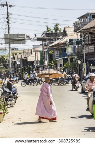 DAWEI, MYANMAR - FEBRUARY 15, 2015: A buddhist nun is crossing a street at Dawei, in the south of Myanmar. She is wearing a parasol. - stock photo