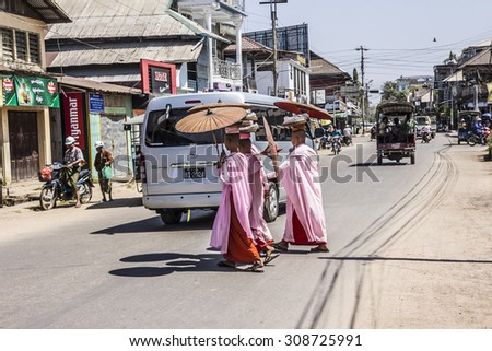 DAWEI, MYANMAR - FEBRUARY 15, 2015: Buddhist nuns are crossing a street  at Dawei, Myanmar. They are wearing parasols. - stock photo