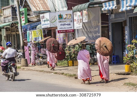 DAWEI, MYANMAR - FEBRUARY 15, 2015: Buddhist nuns are walking along a street  at Dawei, Myanmar. They are wearing parasols. - stock photo