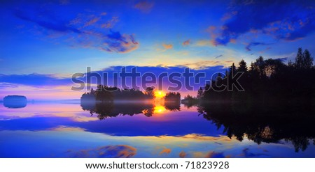 Dawn and mist over the surface of a lake. - stock photo