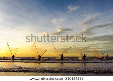 Dawn at Hai Thinh beach, Namdinh, Vietnam. Fishermen fishing in the sea at sunrise. They use a small net to scoop the seafood near the beach. - stock photo