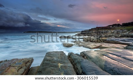 Dawn at Mahon Pool at Maroubra with incoming storm from the east.  It doesn't take much the seas to be churned up in this rocky piece of coastline - stock photo
