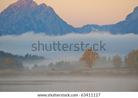 Dawn at Oxbow Bend in Jackson Hole Wyoming with the Grand Tetons in the background on a foggy morning.