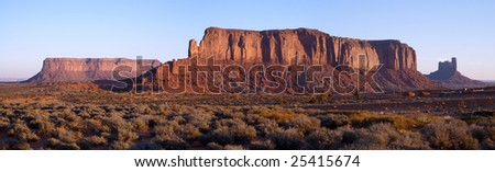 Dawn bathes Sentinal Mesa in warm light in Monument Valley, Navajo Nation. - stock photo