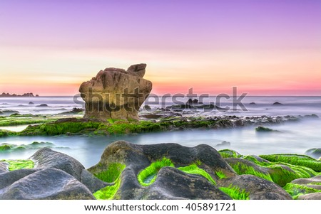 Dawn beautiful moments on stone fossil with sky seven colors, below a large rock overlooking sky, surrounded green algae in reefs interspersed with smooth sea truly welcome new day peaceful - stock photo
