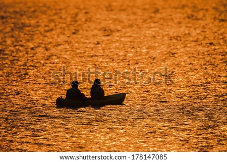 Dawn Colors Dam Waters Teenagers Fishing  Dawn nature's color reflections over dam smooth waters sky clouds landscape with two silhouetted teenagers girl boy fishing - stock photo